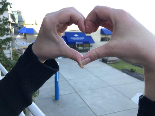 Fingers making a heart over the VIU logo