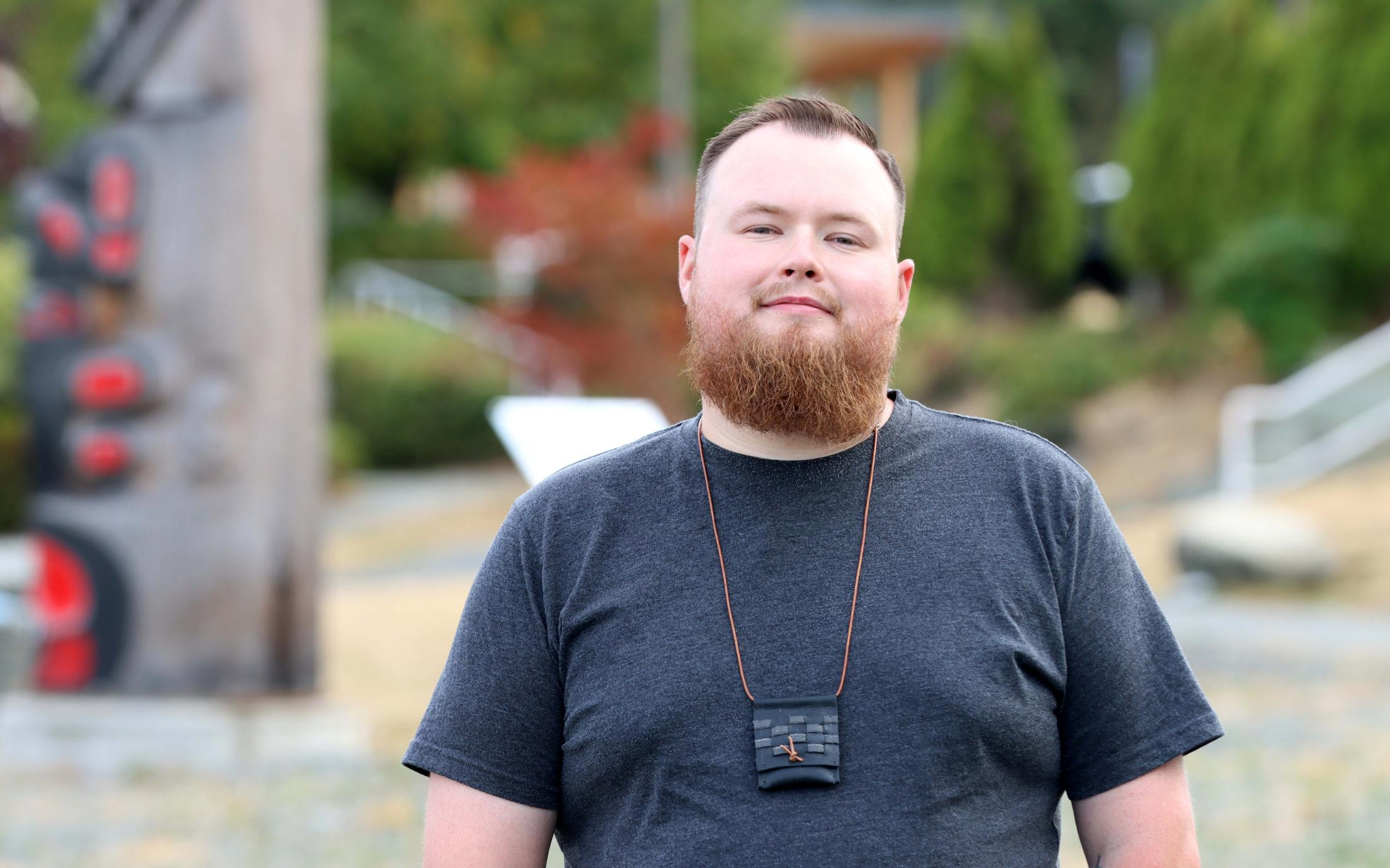Portrait of Aaron Moore in front of totems at VIU Nanaimo campus