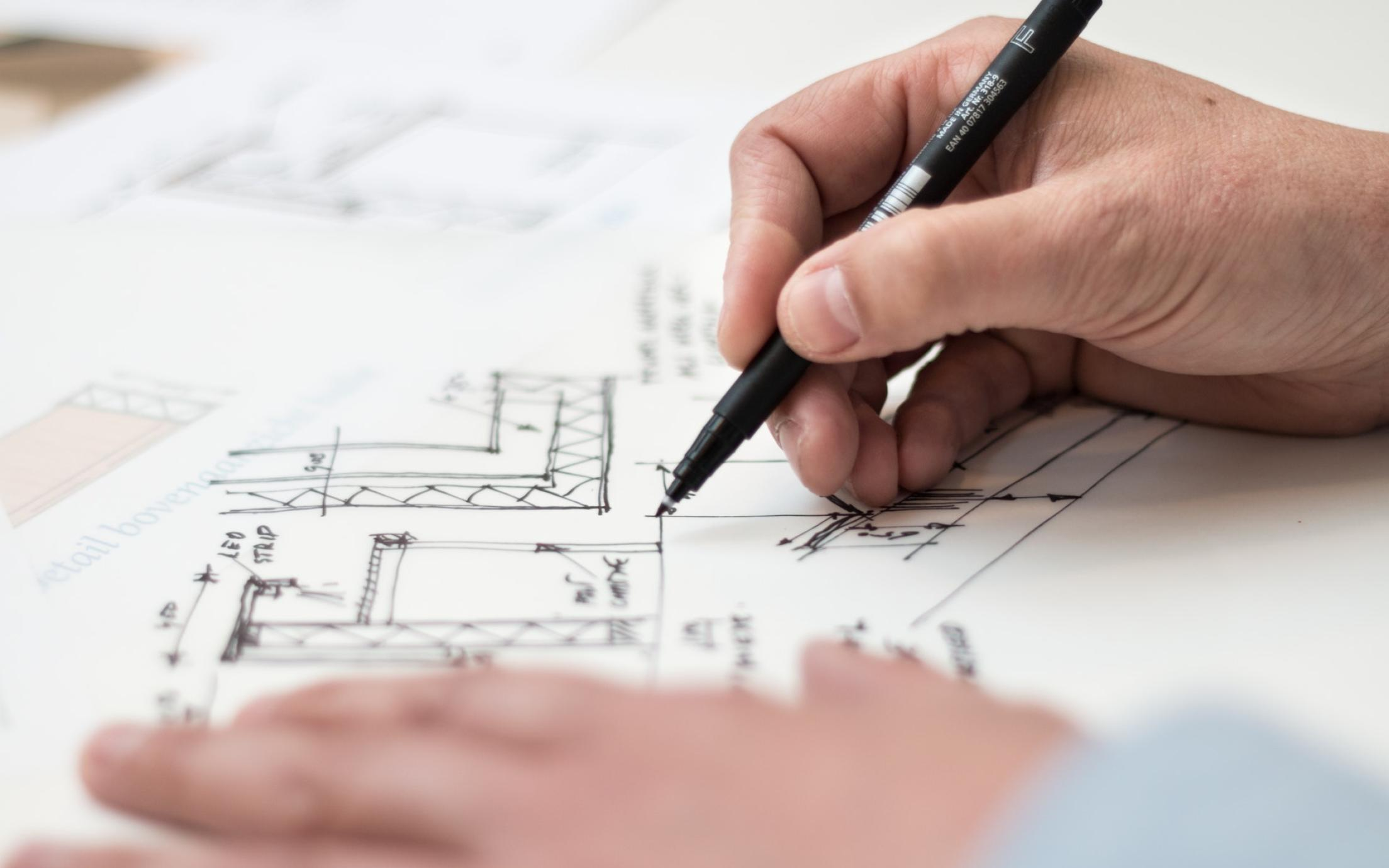 hands sketching an architectural drawing