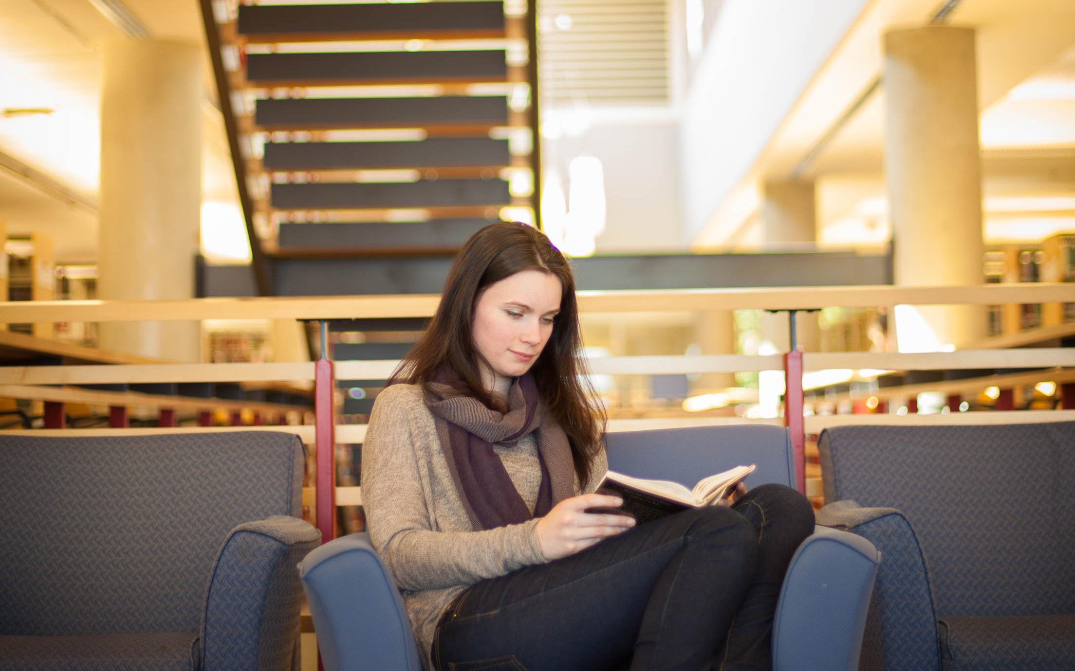 A Bachelor of Arts in English Honours, Major, Minor student studying for her writing courses in the library