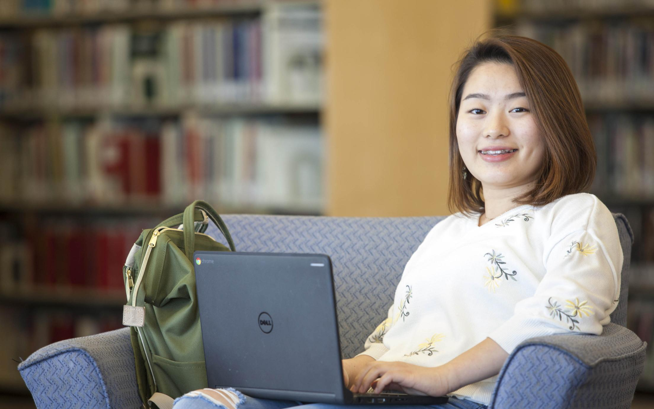 A Student of the Bachelor of Arts, Minor in Digital Media program studying in the library