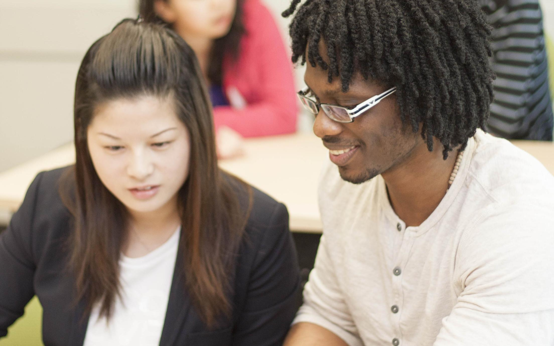 A male student of the Bachelor of Arts, Minor in Media Studies program talking to a fellow student