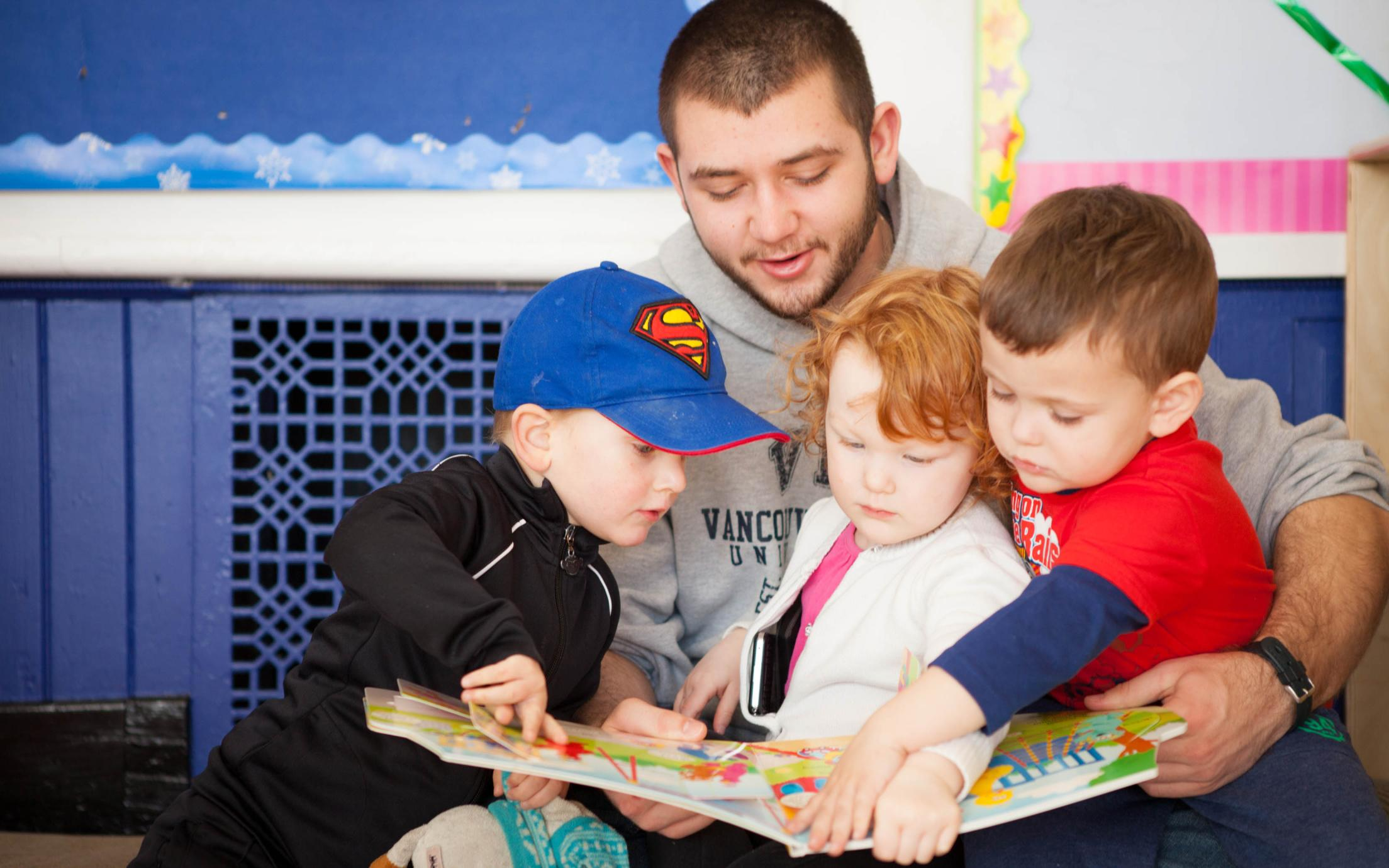 A graduate of the Child and Youth Care program is reading to kids at a family child services center