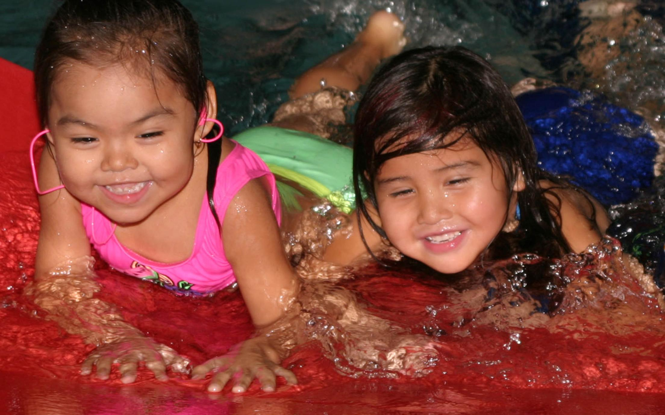 A Child and Youth Care First Nations Worker taking care of two little girls who are having fun at the pool