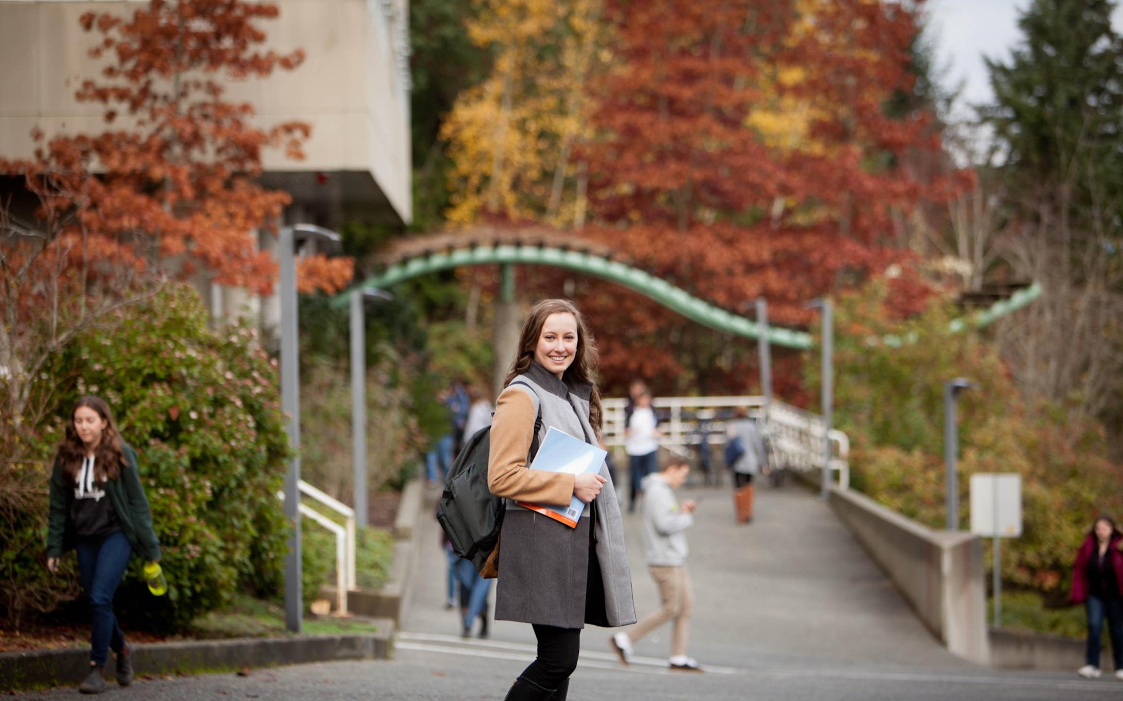 A female student of the Event Management Online Certificate Program carrying around her study material