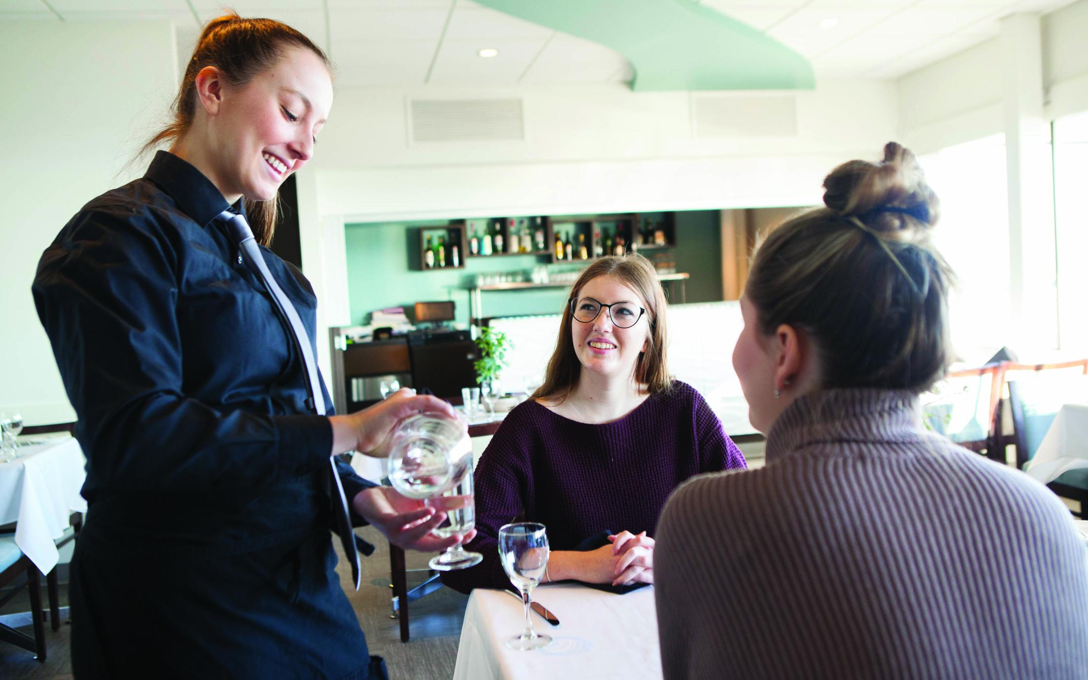 A Student of the Hospitality Management Diploma program serving two women