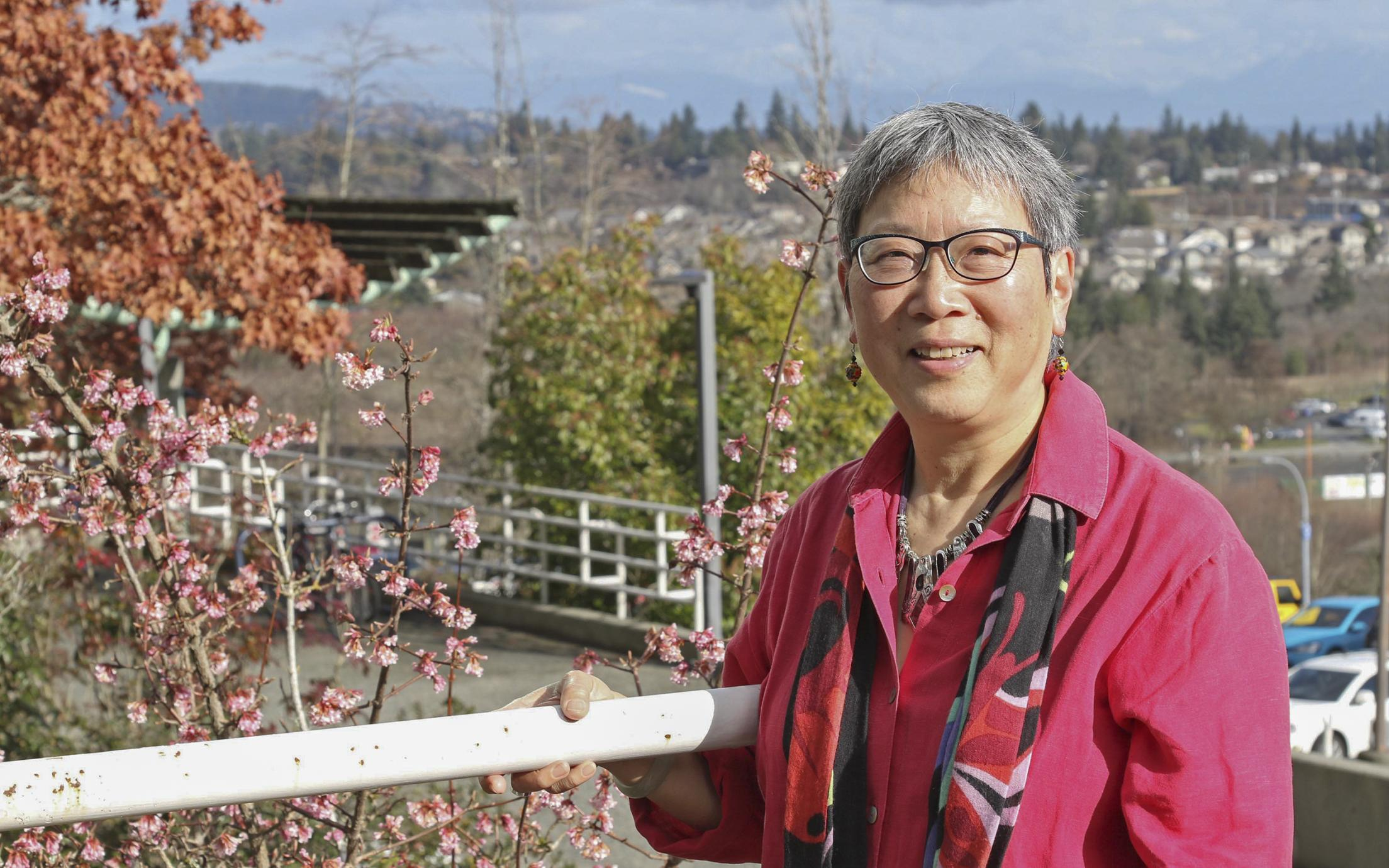 Dr. Imogene Lim stands along a guard rail with the Nanaimo cityscape in the background.