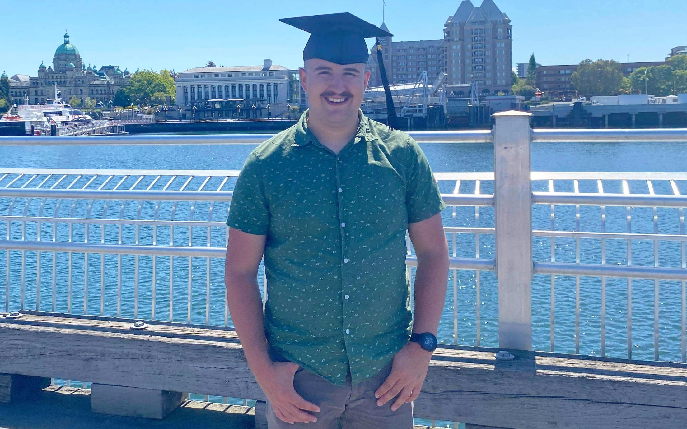 VIU Criminology grad Liam Kenney posing in his grad hat