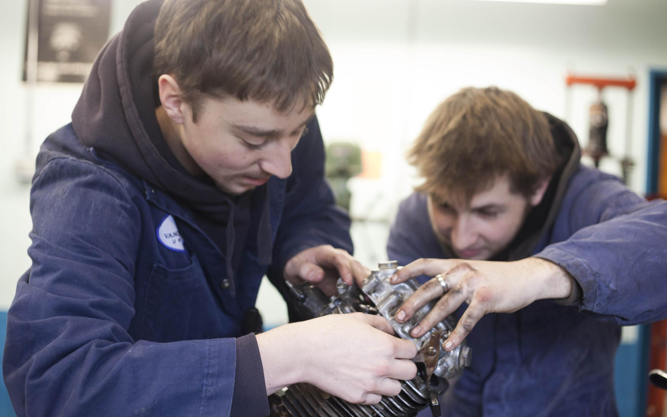 Students of the Marine Technician and Motorcycle Mechanic program repairing on an engine