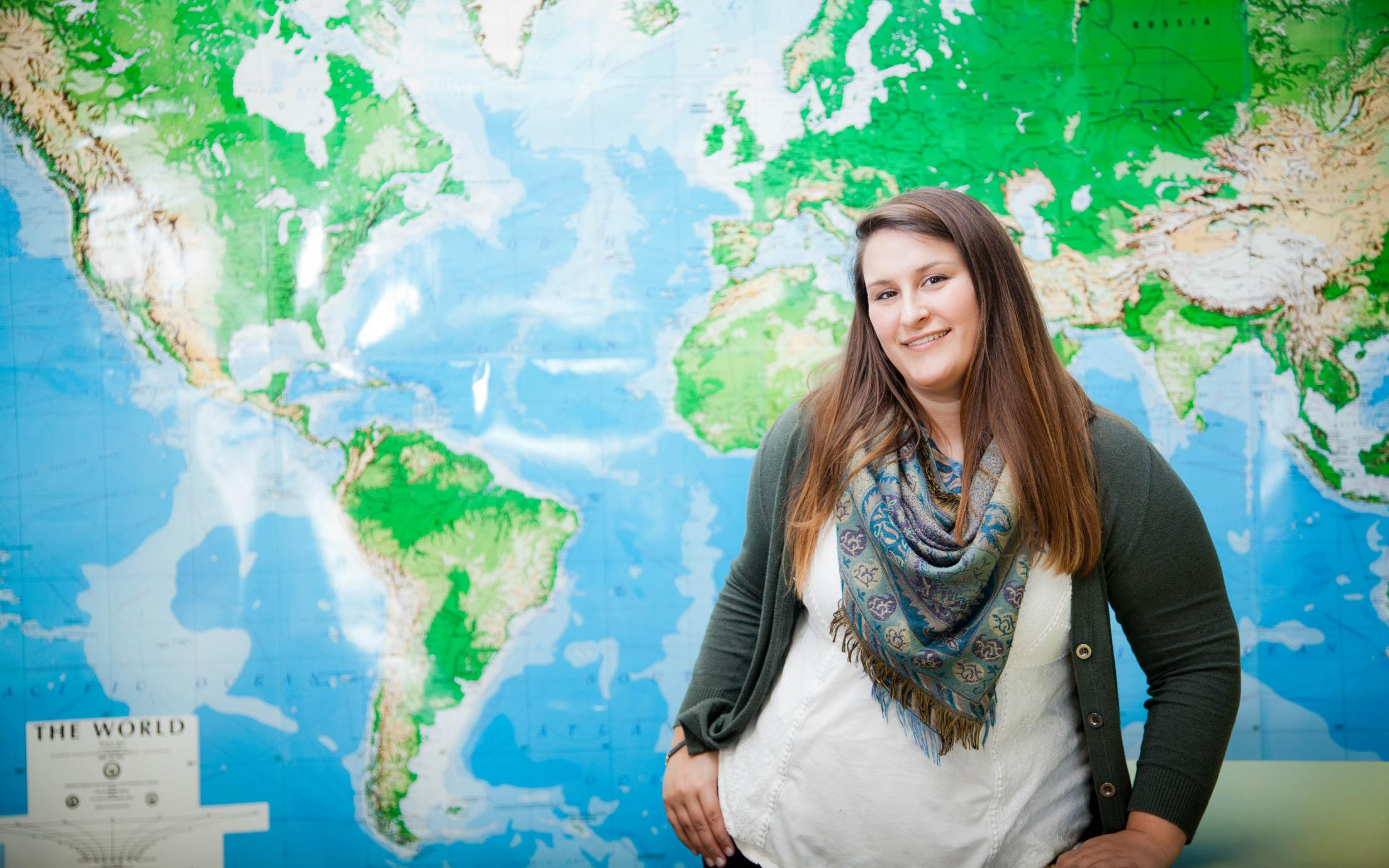 Bachelor of Arts, Geography Major Student, Haley Robinson in front of a world map