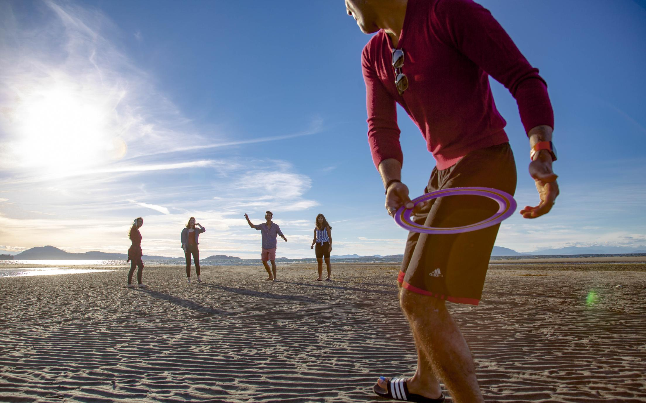 Students play frisbee at a beach