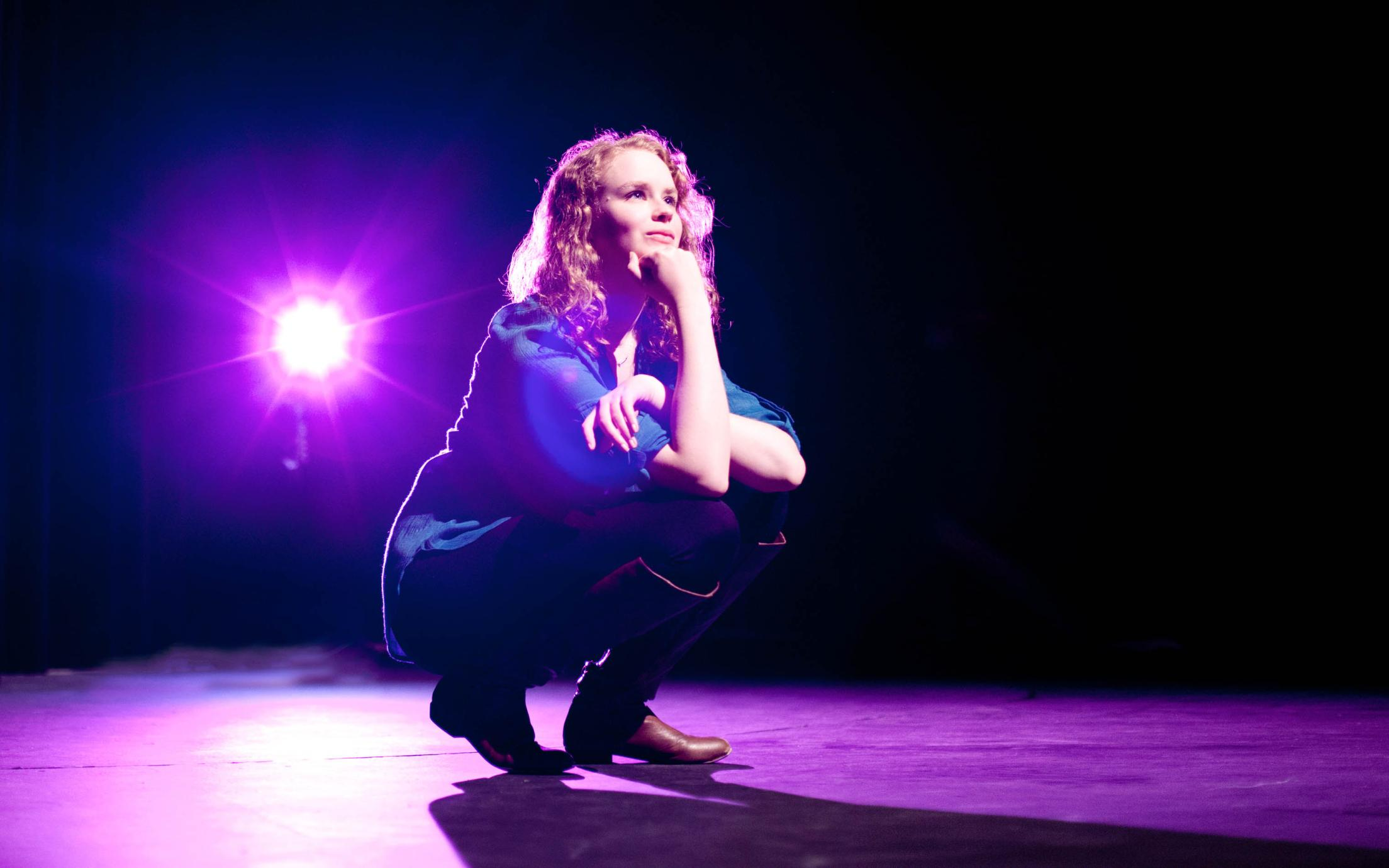A female student of the Theatre program on stage
