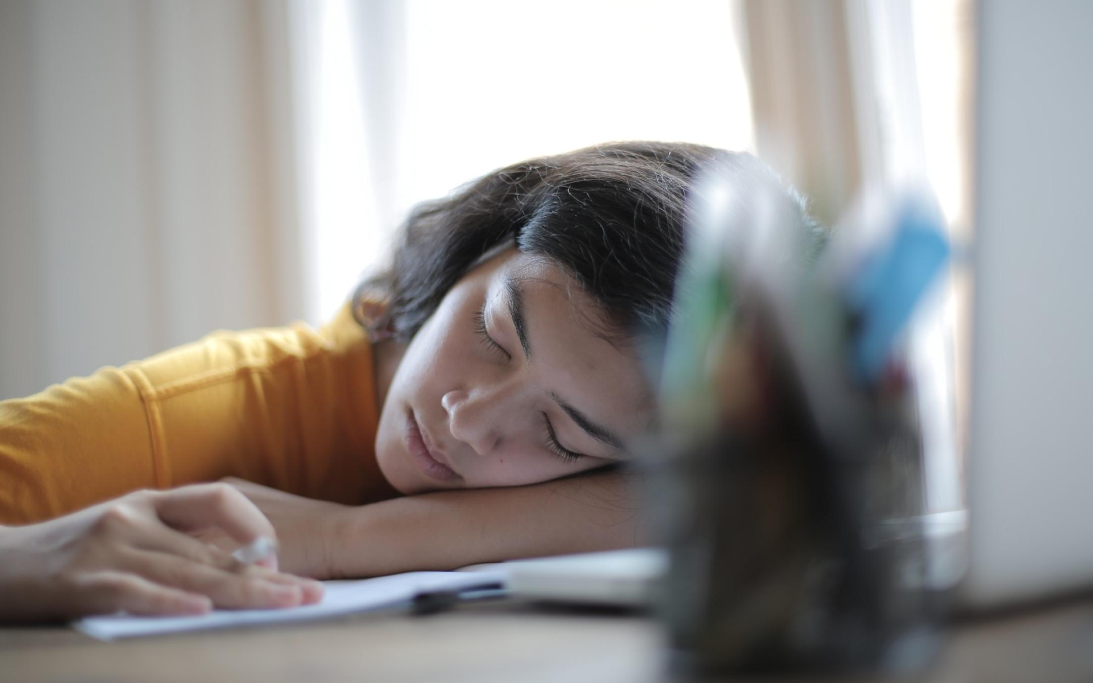 Student sleeping on her books