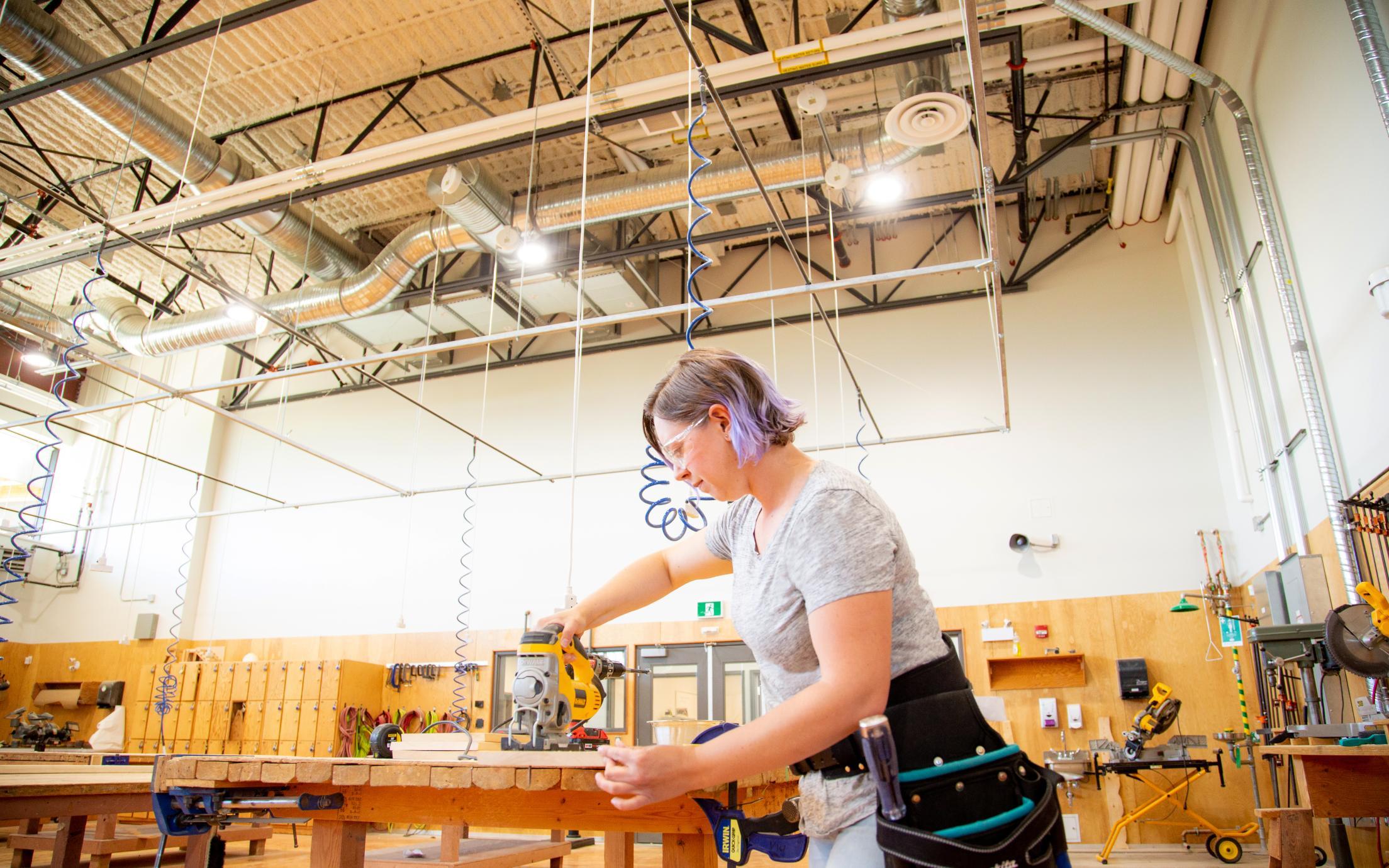 Female cutting a board in carpentry shop