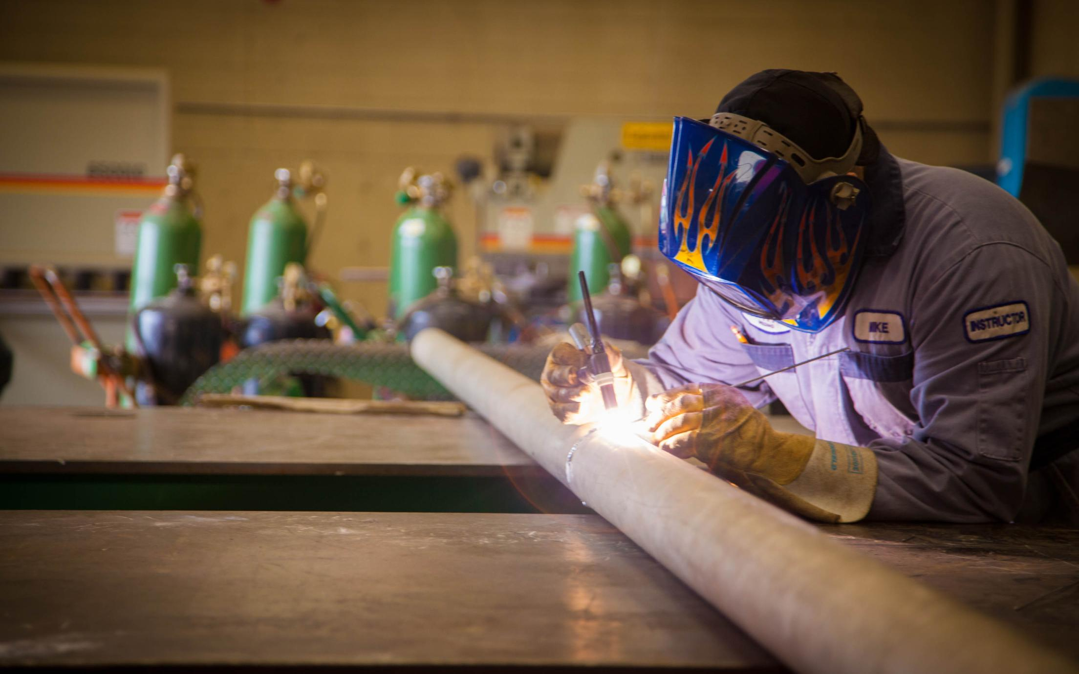 A VIU's Welding certificate student is welding a pipe
