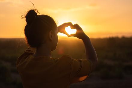 Girl making a heart with her fingers and the sunset poking through