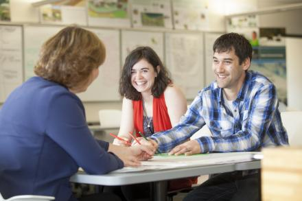 Two graduate students speak with a professor