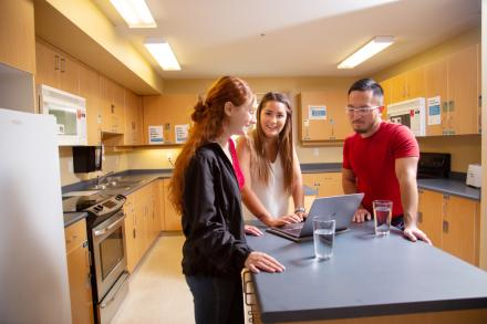 Three students standing around a kitchen island