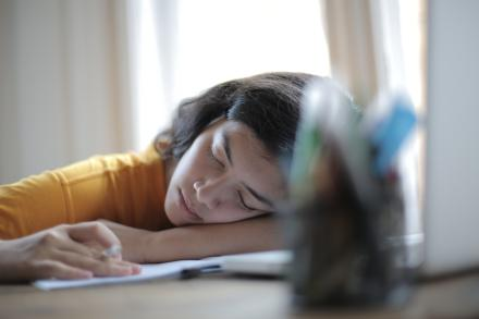 Student sleeping on her books